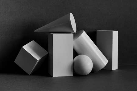 Abstract geometrical objects still life composition. Three-dimensional rectangular prism, cylinder pyramid cube, sphere on black gray background