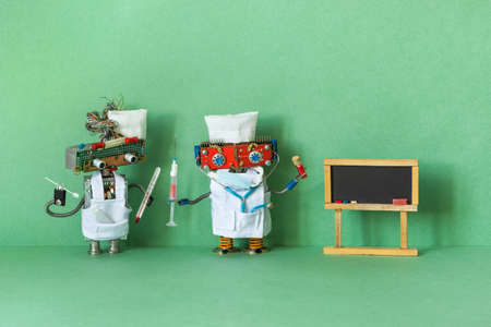 Medic robot holds a thermometer, stick for scraping PCR test. The second doctor is holding a syringe and a test tube with a blood sample. copy space for text on black chalkboard, green background Imagens