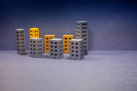 Miniature city with blue yellow brown houses on blue evening background. Abstract urban architecture landscape, simplified town layout with different size buildings, skyscrapers with many windows. Blue background