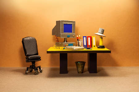 Toy office workplace. Vintage computer, empty blue screen monitor, pc mouse keyboard, archive files. Desk lamp. Comfortable black leather manager chair. Imagens