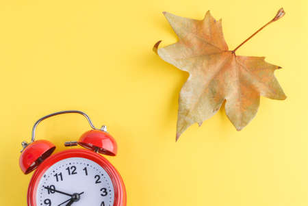 Red alarm clock and a dry autumn leaf on yellow. Stock Photo
