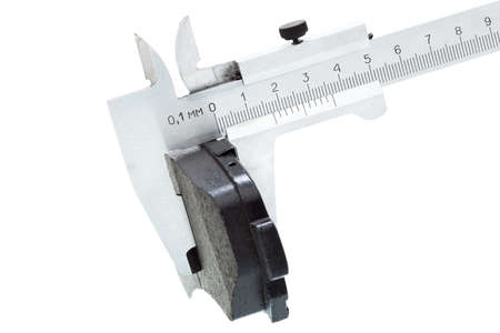 brake caliper: brake pads of the car on a white background, measurement by a caliper of thickness, isolated image nobody.