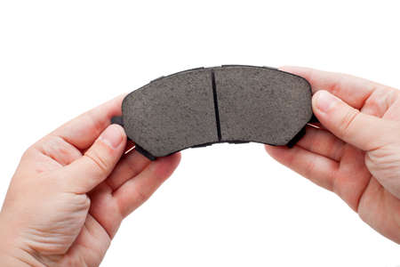 hand brake: Brake pads in the engineers hand, isolated. Stock Photo