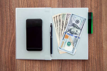 denomination: The daily log with denomination hundred, fifty, twenty, and ten dollars and a credit card on a wooden table with black business smartphone and pen.