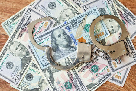 detention: Dollars of hundred and fifty dollars lie on a floor and from above handcuffs for detention of the corrupt official on polichny are put. Stock Photo
