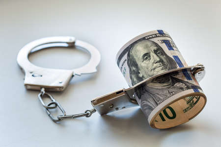The dollars of hundred dollars twisted in a tubule and chained in handcuffs.