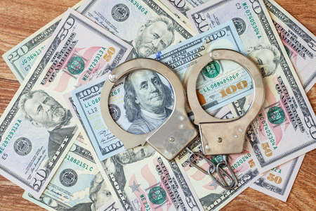 corrupt: Dollars of hundred and fifty dollars lie on a floor and from above handcuffs for detention of the corrupt official on polichny are put. Stock Photo