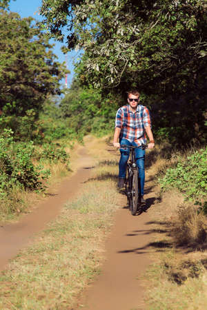 goes: The young guy goes on the forest road by black bicycle to a sunny day, a wearing spectacles, plaid shirt and blue jeans, with wooden hours on hands. Stock Photo