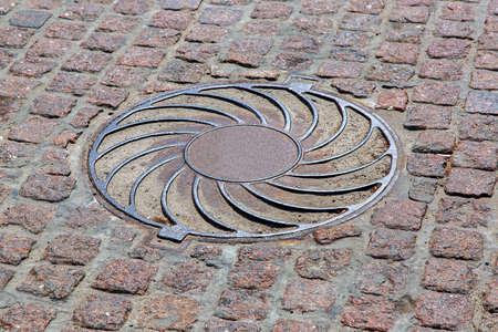slabs: Rusty circle iron manhole,  cover on paving slabs, nobody.