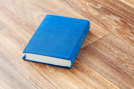The book blue colour in a firm cover leit on a wooden surface of a table, the top view sideways.