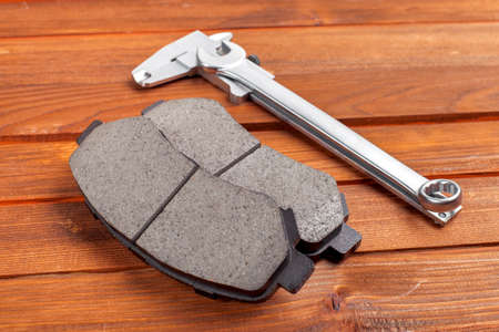 brake caliper: The tool for replacement of brake pads: a spanner wrench, a caliper and spare parts for the car on a wooden background from boards.