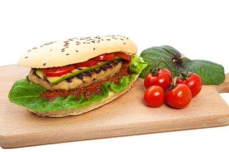 mayonesa: Sandwich con chuleta de carne en una tabla de cortar con una fila de mentir tomates sobre un fondo blanco, nadie. Foto de archivo