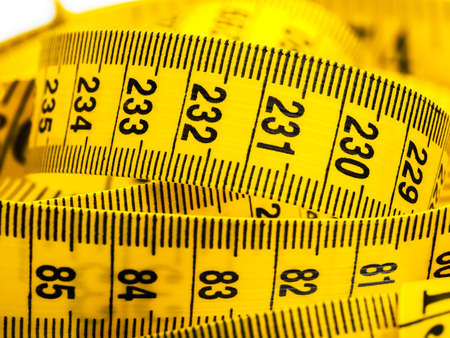 Centimeter of yellow color from fabric for measurement of length and volume on a white background.