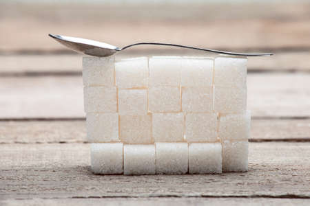 The refined sugar put by a pyramid on a wooden table from old boards, with a teaspoon. Stock Photo