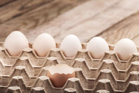 Eggs in a paper tray on a wooden table from old boards.
