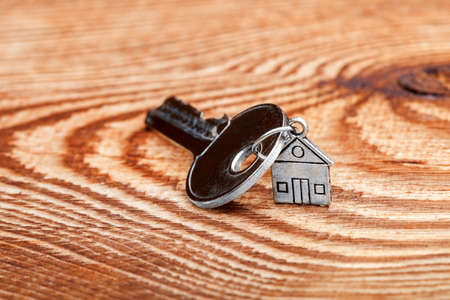 Key about a charm in the form of the house on a wooden table.