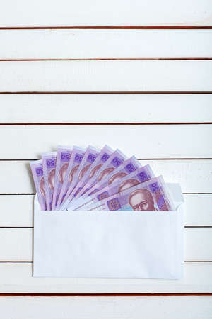 payola: Cash in an envelope, the denomination of ukrainian hryvnia on a table from white wooden boards. Stock Photo