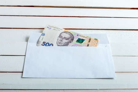 Cash in an envelope, the denomination of ukrainian hryvnia on a table from white wooden boards. Stock Photo
