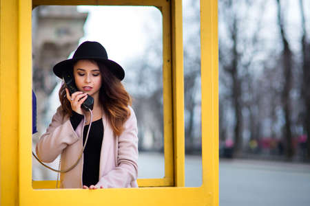 The girl in a coat and a black hat on the head costs in a yellow public callbox and hold the handset in the right hand.