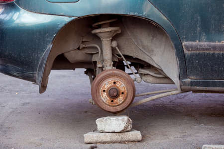 Car without wheels costs on brick, old rusty car brakes in poor condition.
