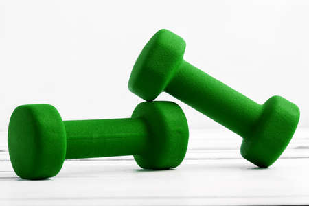 dumbbells weight for fitness green color on white wooden board. Stock Photo