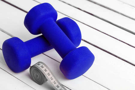 dumbbells weight for fitness blue color with tape measure on white wooden board.