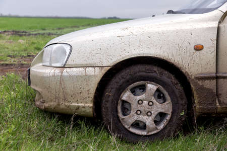the dirty car, the car costs on a green grass in the field, the right front fender close up splodgy with dirt. Reklamní fotografie