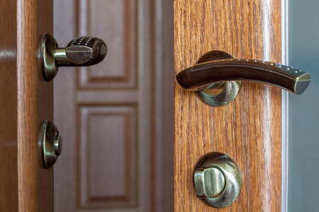 door with the handle and the lock close up on a wooden door with a glass insert. Stock Photo
