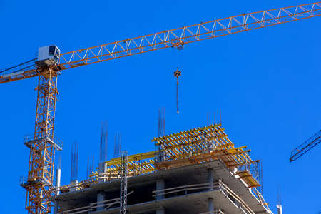 High rise building under construction, seen from below against blue sky. Stock Photo