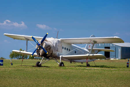 The old plane, agricultural aeroplane costs in the field in a green grass. Stock Photo