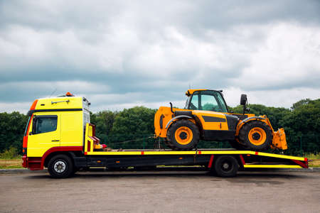 moving truck: The tow truck on the platform transports the new tractor, the equipment for technical and agricultural works.