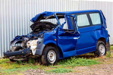 The crash car, broken minibus after accident. Failed blue van on country road, near a metal gray fence. Stock Photo