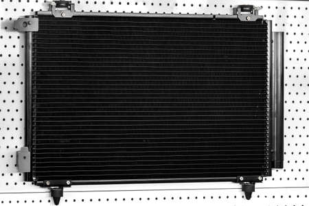 Engine cooling radiator black color, car spare part on stand.