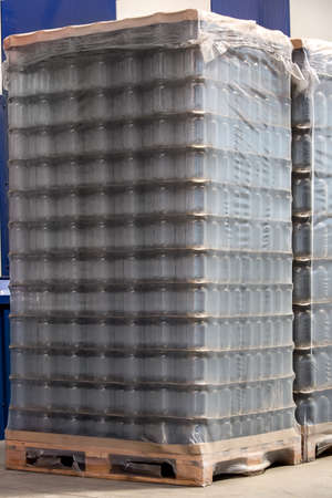 empty warehouse: pallet with glass jars for preservation or liquid food, the packed party for transportation. Stock Photo