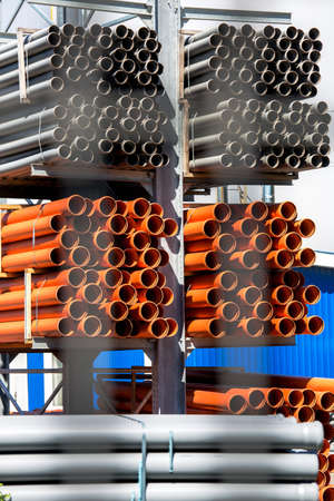 The plastic pipes put into racks into storage outdoors. Stock Photo