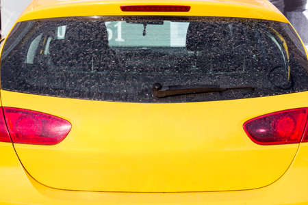 dirty rear glass of the car of yellow color, back view. Stock Photo