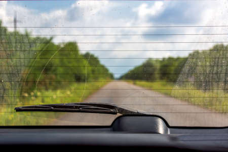 View of a rear glass of the car with the dirty  back glass with wiper, overlooking the road. 版權商用圖片