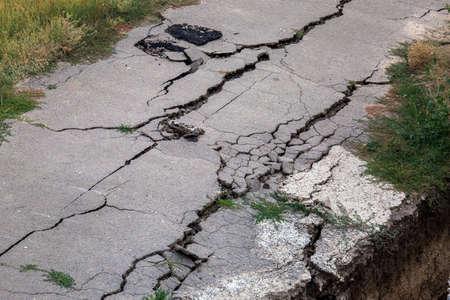 Consequences of a natural cataclysm of a landslide of soil, crack asphalt paving.