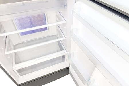 The refrigerator, empty glass shelves and a tray for vegetables, top view inside the refrigerator. 版權商用圖片