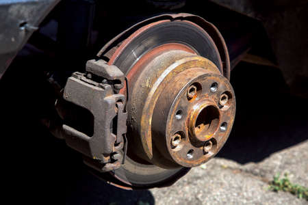 Brake disc with saddles and shoals close-up on the used car.