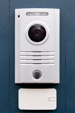 An intercom with a call button and a light colored camera is installed on the iron dark gate with an access card receiver, the front view is close-up. Stock Photo