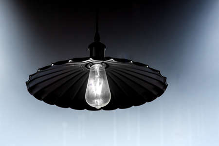 Black iron lamp with a spiral lamp, chandelier with a glowing lamp against the background of the wall.