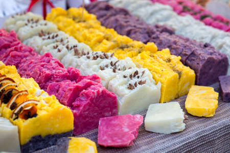 Handmade soap laid out on the counter of the store and cut into pieces, multi-colored pieces of soap close up. Stockfoto
