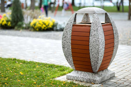 an oval-shaped garbage can on a concrete stand decorated with boards against the background of a pedestrian sidewalk of a park area. Archivio Fotografico
