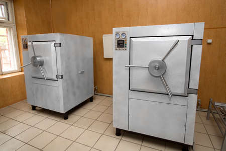 Industrial large autoclave for disinfection of medical supplies, 2 devices of the medical industry in the room.