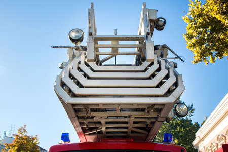 Fire truck ladder in folded state close-up against a blue sky. Stock Photo
