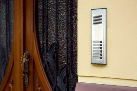 An intercom with a microphone and call buttons close-up on a yellow wall at the entrance wooden door with glass and a wrought-iron grille. Stockfoto