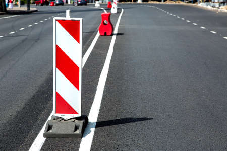 New asphalt pavement and fresh road markings with a white-red safety sign enclosing oncoming traffic. Stock Photo