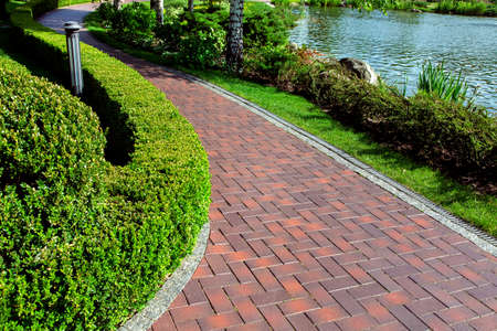 pedestrian pavement with tiles and drainage system on the left a hedge of deciduous bushes on the right of a flower bed with a lawn in the background an artificial pond with water.
