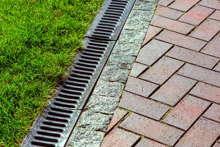 iron drainage net between paving slab and green lawn. Stock Photo